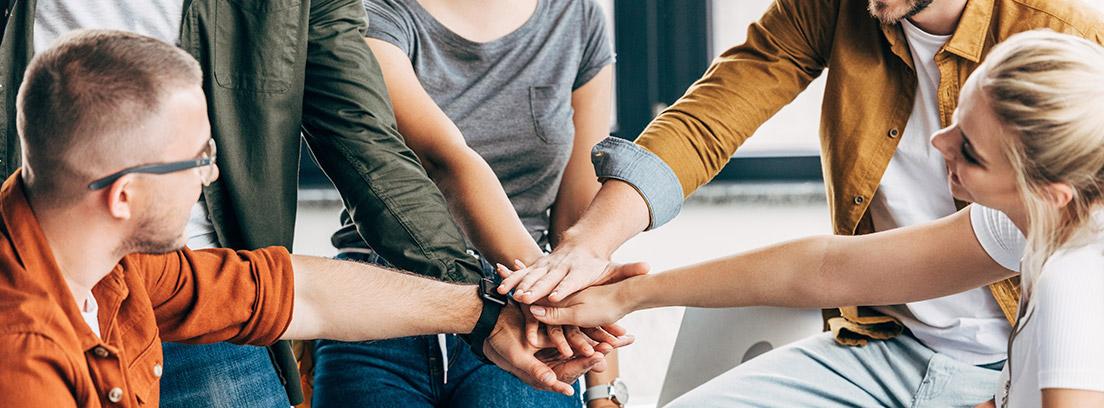 Varias personas de un equipo de trabajo juntando sus manos