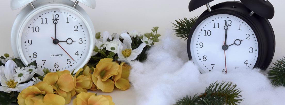Reloj blanco con flores marcando las tres y reloj negro con ramas de pino y nieve marcando las dos