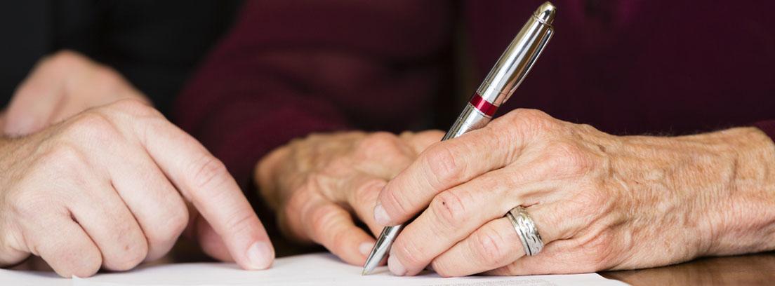 Persona mayor firmando documentos