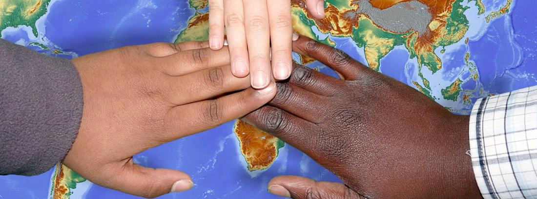 Manos de niños de distintas razas sobre un mapa mundi