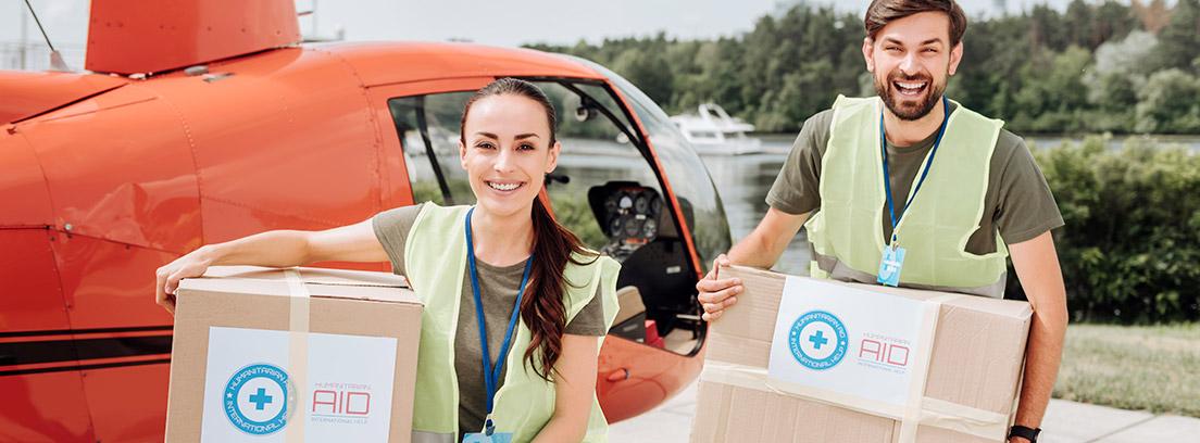 Dos jóvenes transportando cajas con ayuda humanitaria