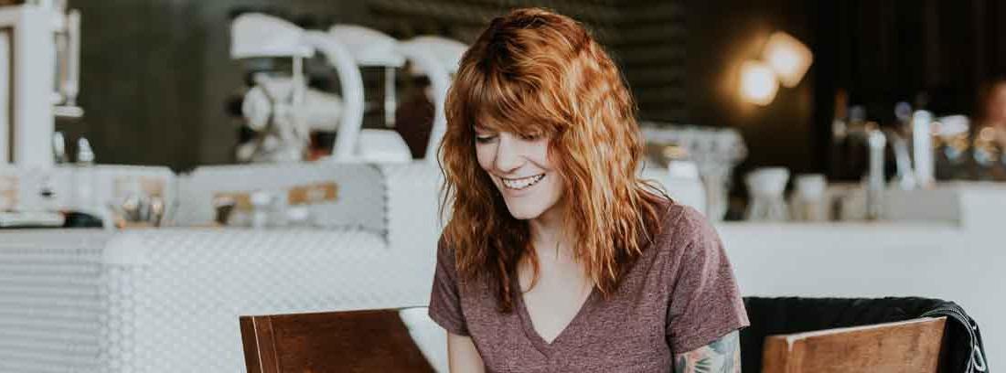 Mujer con gesto sonriente mira la pantalla de un portátil