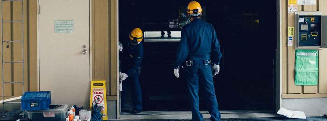 Operarios con monos azules y cascos amarillos trabajando en una puerta