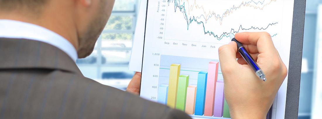 Hombre de espaldas mirando unos gráficos con el índice de endeudamiento de una empresa