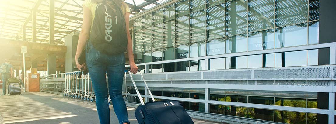 Mujer con mochila y arrastrando maleta con ruedas