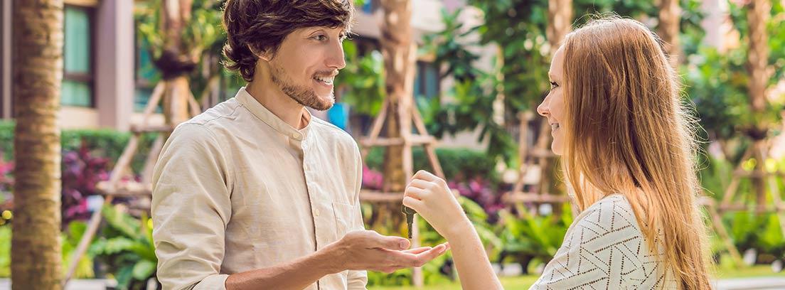 Mujer da unas llaves a hombre frente a ella