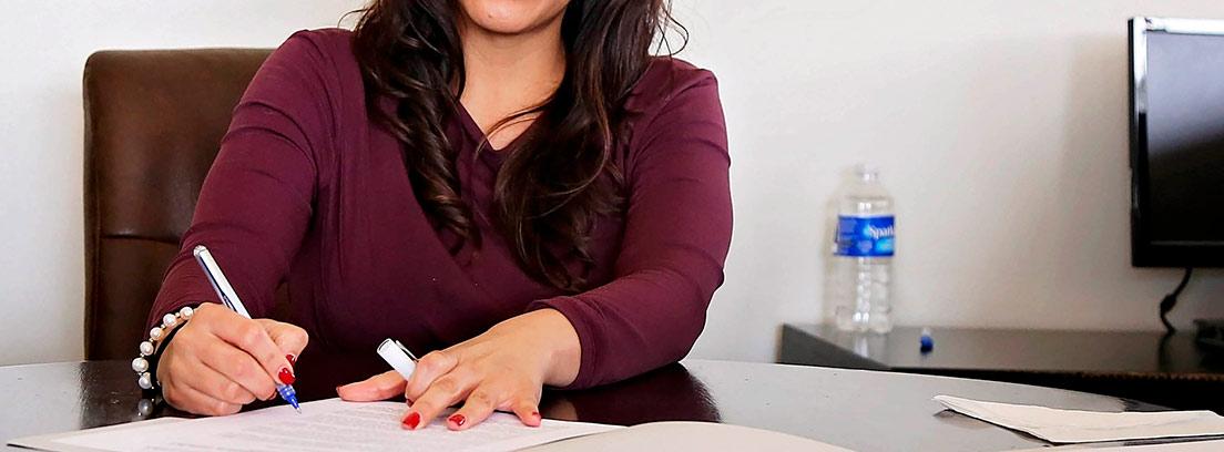 Mujer escribe sobre papeles en una mesa de oficina