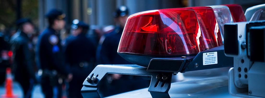 Un coche de Policía y agentes de servicio