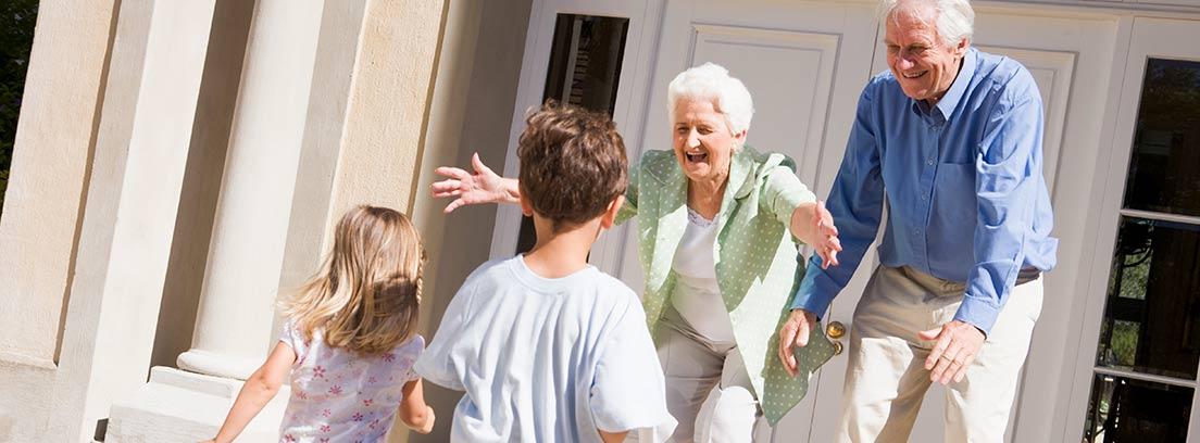 Pareja de abuelos recibiendo a sus nietos, todos vestidos de blanco.