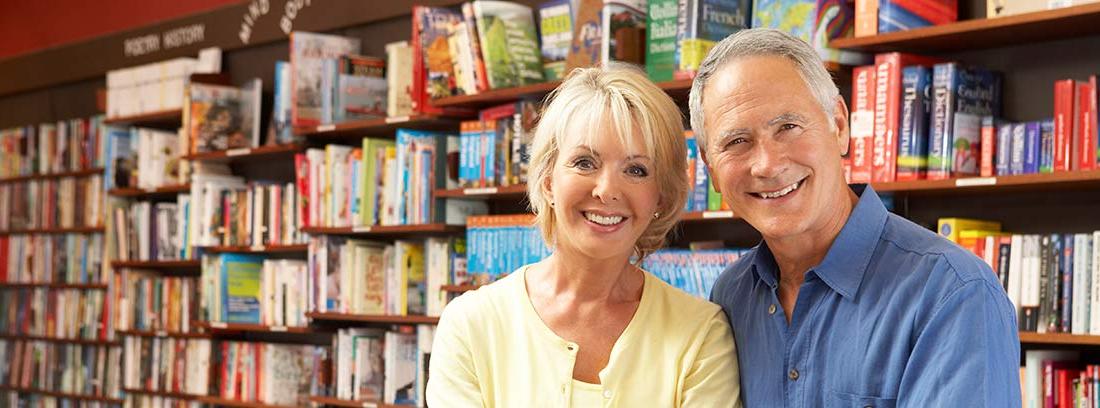 Hombre y mujer senior detrás del mostrador de una librería