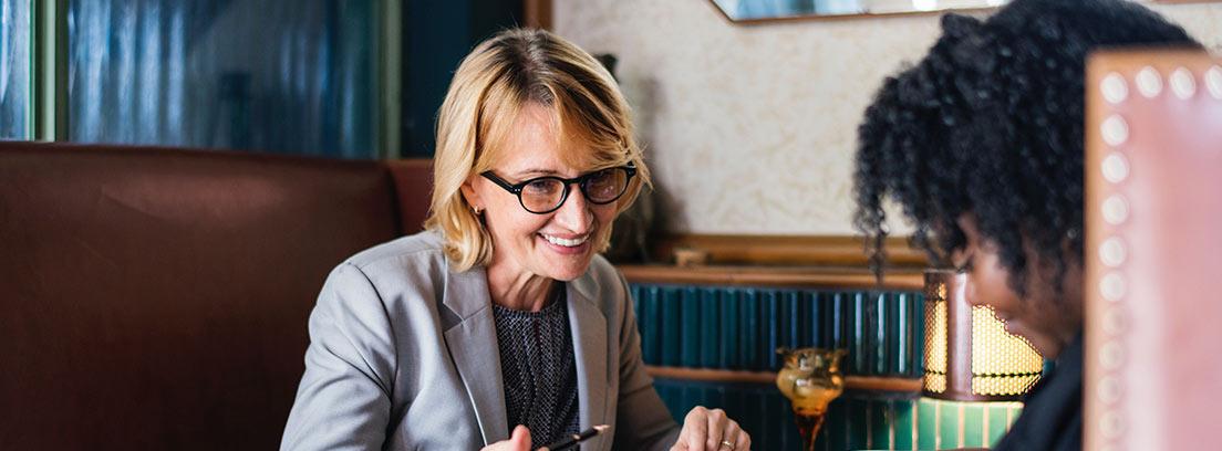 Mujer con agenda sobre mesa sentada frente a otro que señala papeles