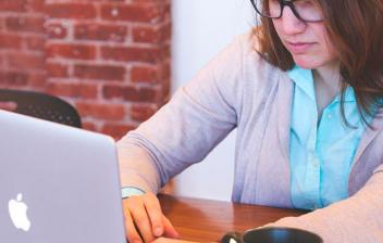 Mujer con gafas delante de ordenador portátil