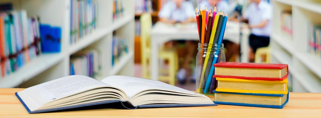 Primer plano de libros y lápices en una biblioteca con tres alumnos al fondo