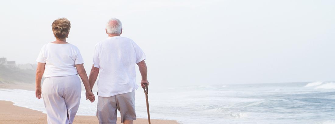 Dos personas mayores de espaldas caminando por la playa cogidos de la mano