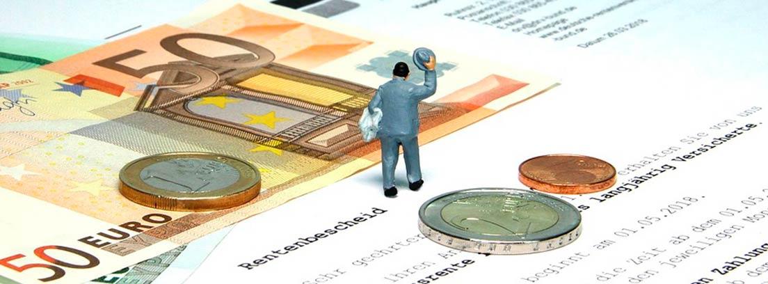Muñeco con traje y sombrero sobre varios papeles, billetes y monedas de euro