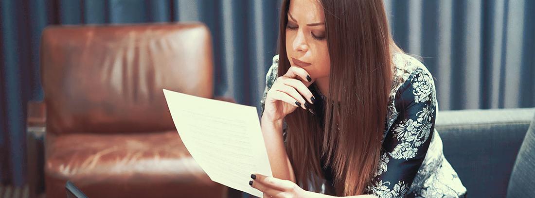 Mujer sentada con la mano sujetando la barbilla mirando un papel con gesto pensativo