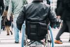 Persona en silla de ruedas atravesando un paso de peatones concurrido