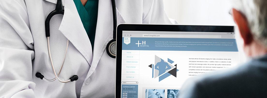 Persona con bata blanca y fonendoscopio señala pantalla de ordenador frente a otra