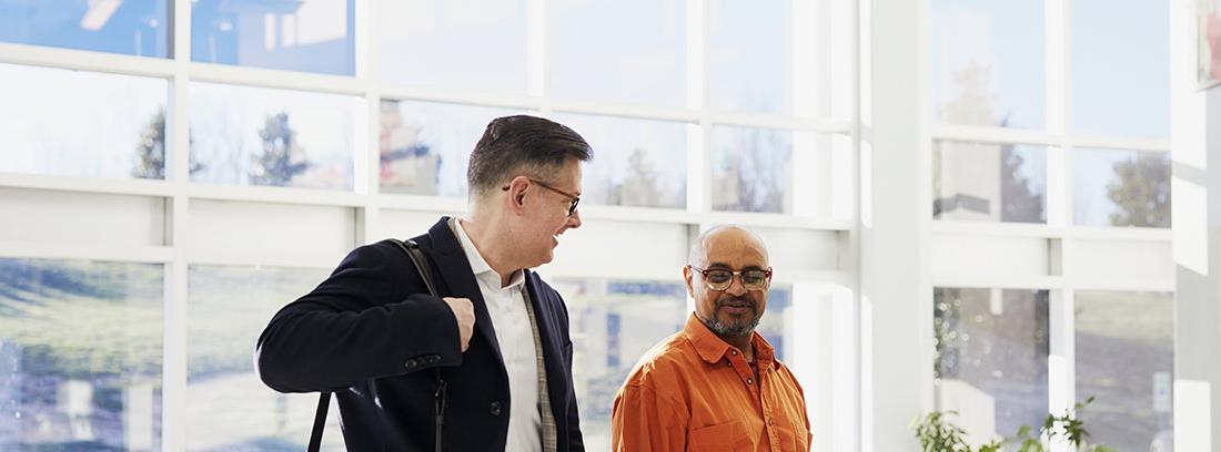 Hombre con cartera al hombro junto a otros andando por interior oficina