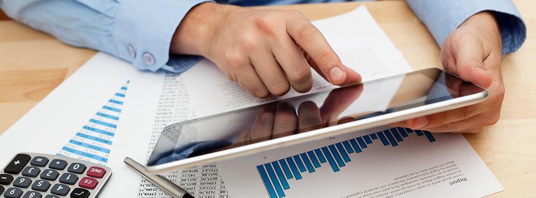 Hombre en una mesa mirando una tablet, unos papeles con gráficos y una calculadora