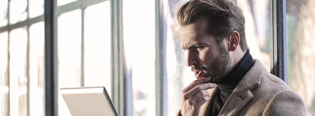 Hombre con mano sobre el mentón y un ordenador portátil sobre las rodillas