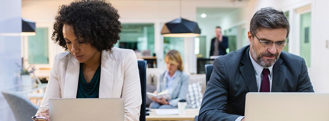 Varias personas con ordenadores trabajando en una oficina