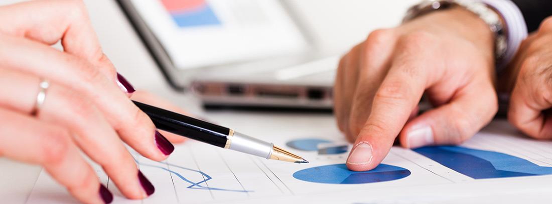 Mano de mujer con un boli sobre unos papeles y mano de hombre señalando un gráfico financiero