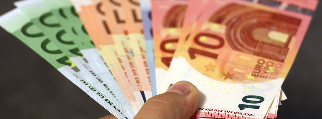 Mano sujeta diferentes billetes de euro