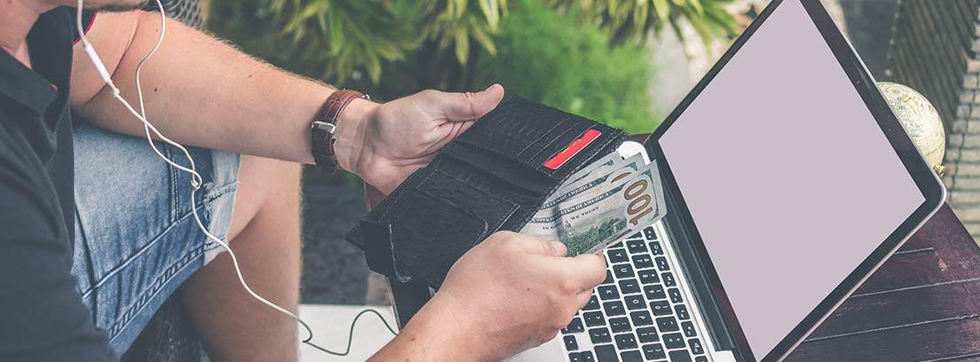 Hombre coge dinero de su cartera delante de ordenador portátil