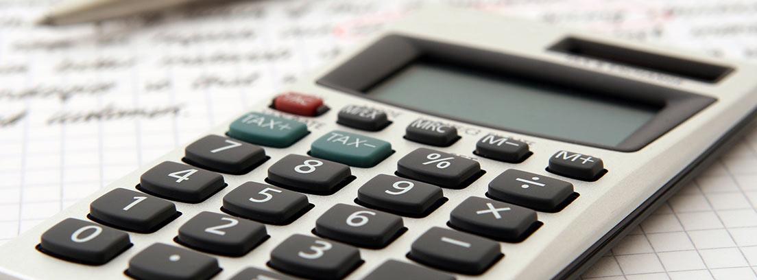 Calculadora sobre hoja de papel y junto a bolígrafo