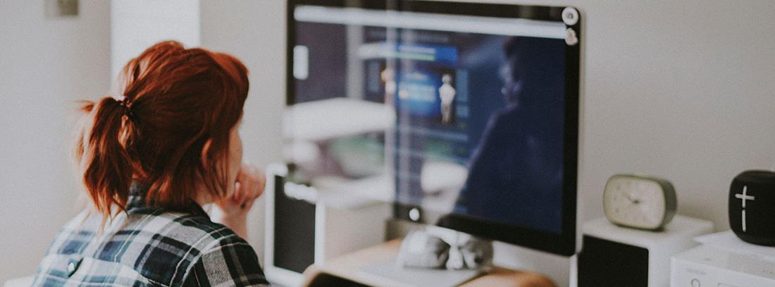 Mujer mira pantalla de ordenador con mano sobre el ratón