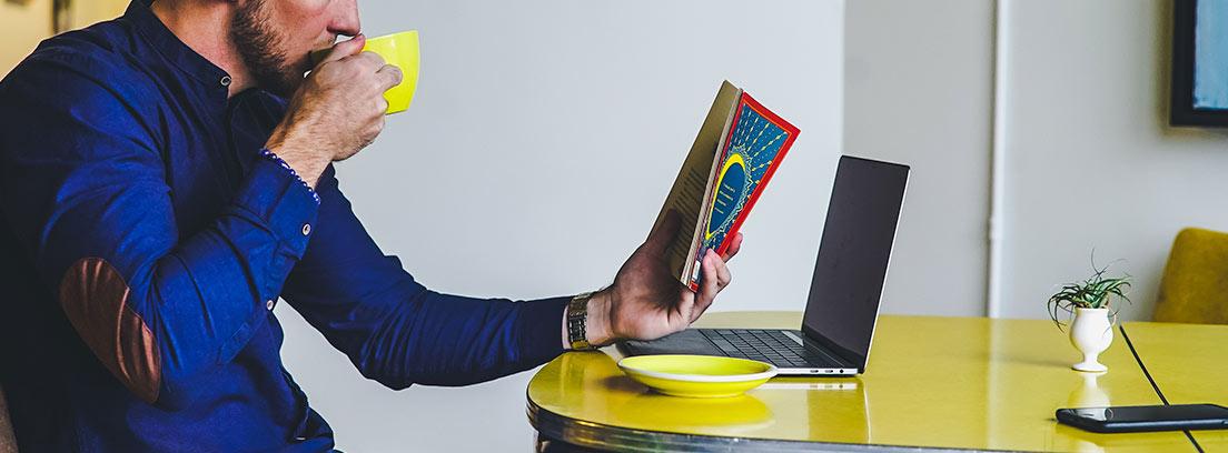 Hombre bebiendo de taza amarilla, sentado delante de ordenador portátil y mirando un libro