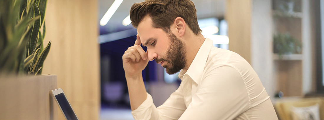 Hombre con mano sobre la sien sentado frente a un ordenador portátil
