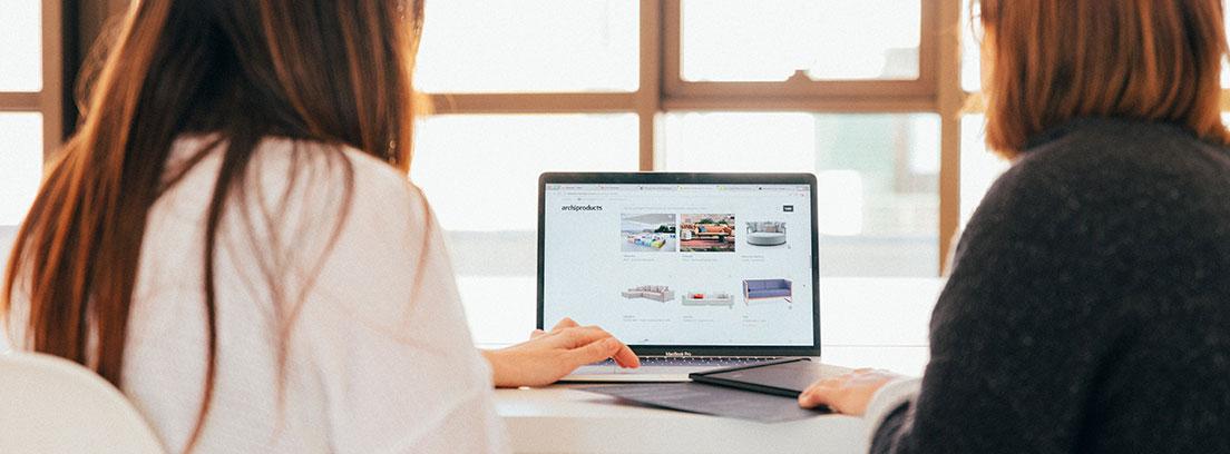 Dos personas sentadas y de espaldas miran hacia un ordenador portátil