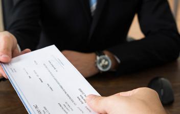 Una persona con traje dando un cheque conformado a otra persona