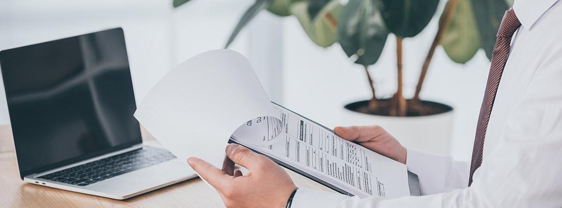 Hombre sujetando una carpeta con documentos sentado a una mesa con un ordenador