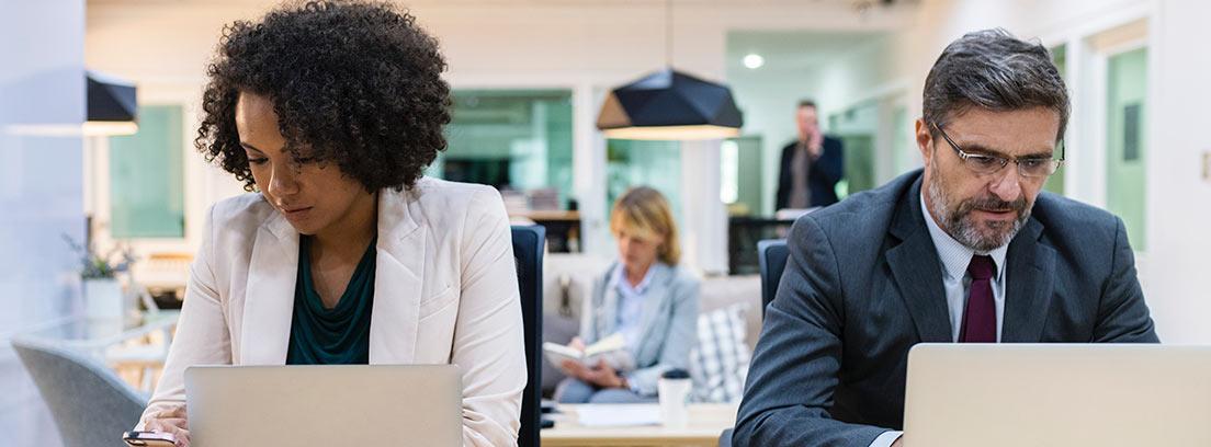 Hombre y mujer sentados en sus puestos de trabajo en una oficina