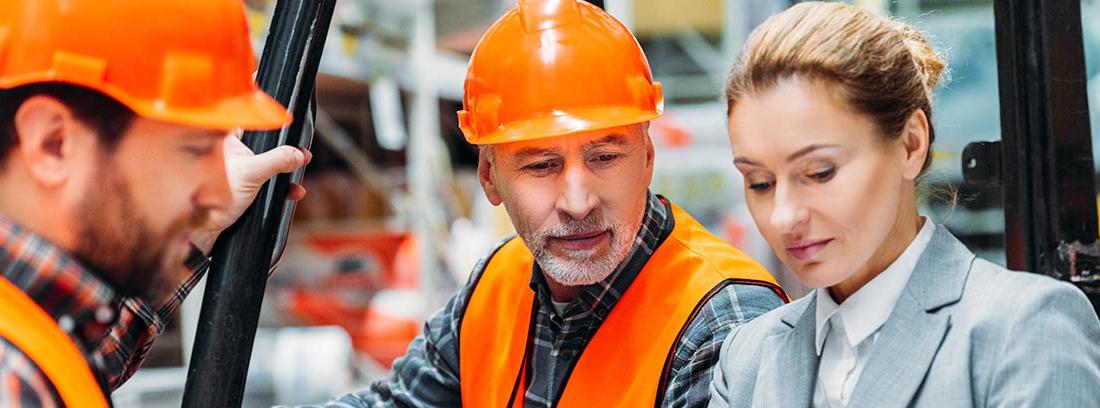 Inspectora de trabajo mirando un cuaderno junto a dos trabajadores con chaleco y casco
