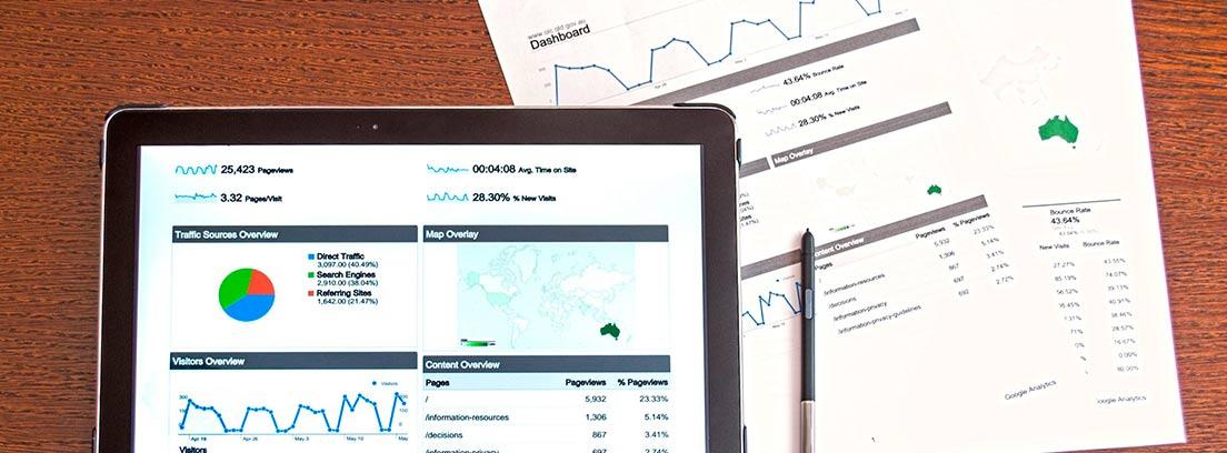 Tableta con índices y gráficos junto a hojas también con datos económicos