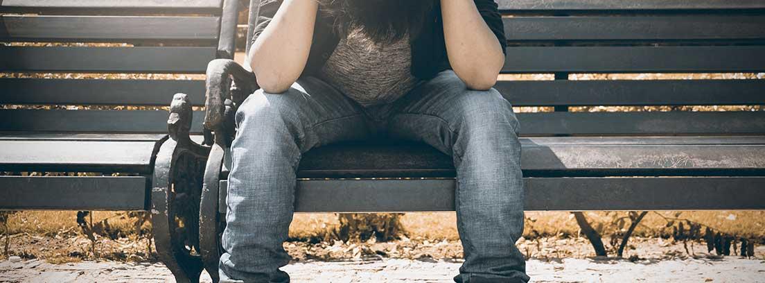 Persona sentada en banco con la cabeza entre las manos