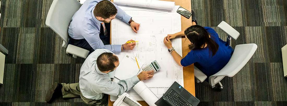 Trabajadores reunidos en torno a una mesa de oficina