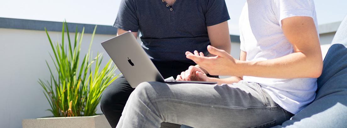 Hombre con ordenador portátil sobre las rodillas junto a otro