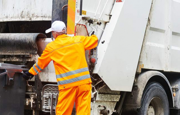 Persona con uniforme naranja junto a contenedor de basura y camión