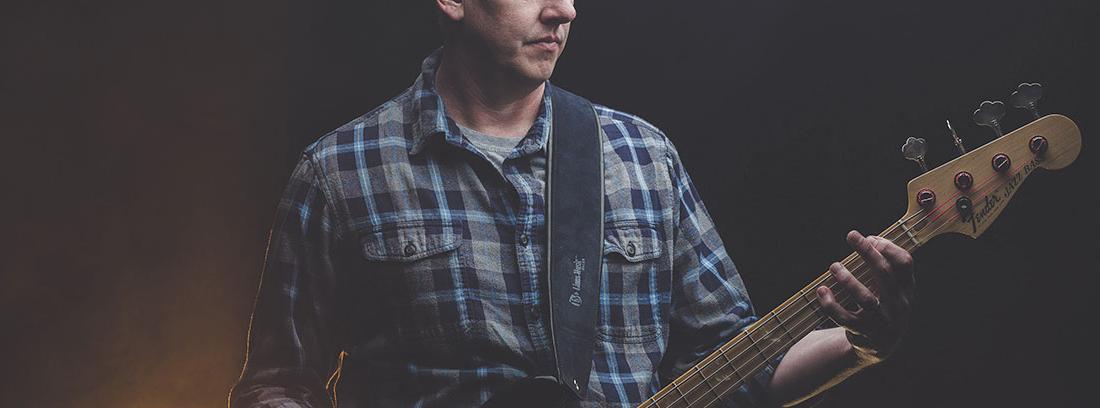 Hombre con camisa de cuadros toca guitarra eléctrica