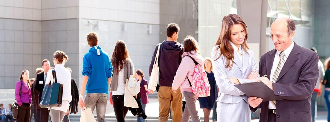 Hombre y mujer leyendo unos documentos y varias personas caminando por la calle