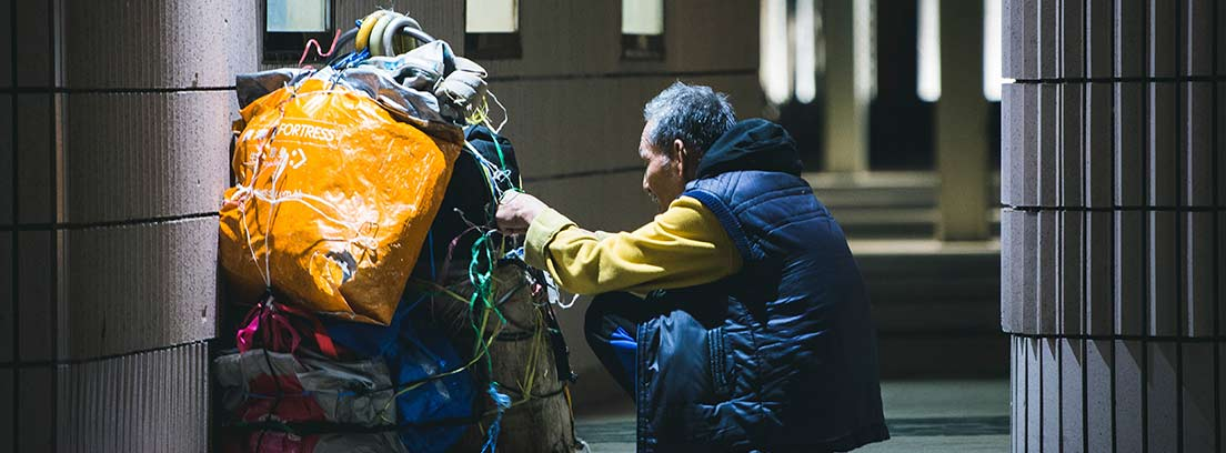 Hombre sentado en la calle coloca cuerda sobre un motón de bolsas apiladas