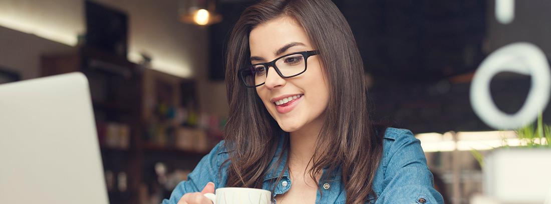 Mujer con una taza de café mirando un ordenador