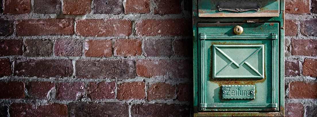 Buzón de correos sobre una pared de ladrillo