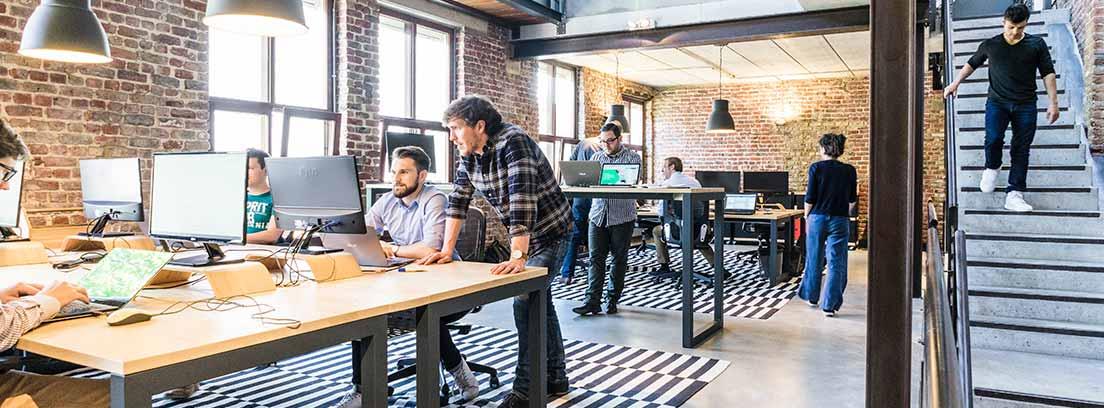Espacio con mesas y sillas con personas trabajando delante de ordenadores