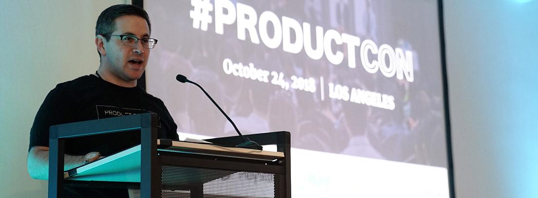 Hombre con gafas apoyado en un atril con micrófono y delante de pantalla